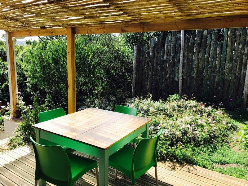 terrasse ensoleillée couverte avec vue sur le jardin, l'endroit idéal pour le petit déjeuner ou le dîner aux chandelles.