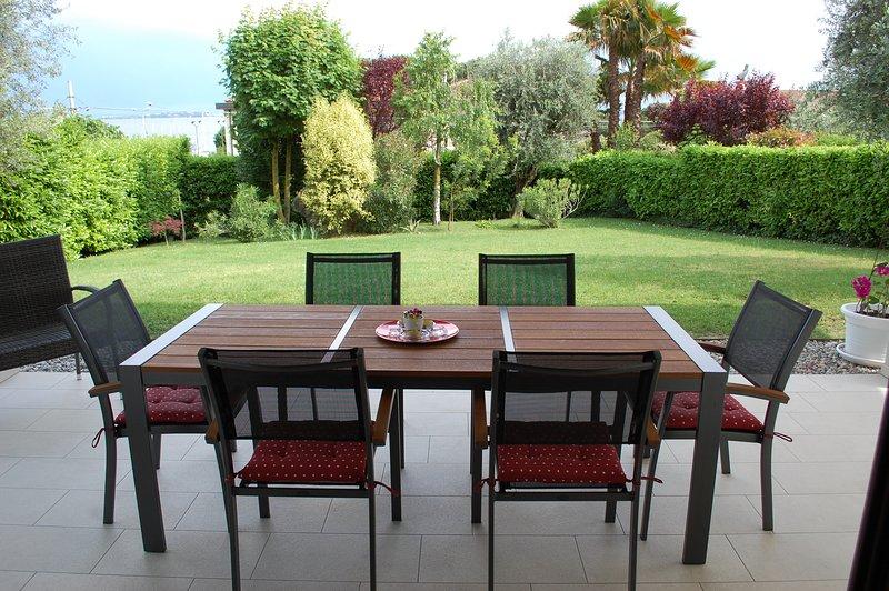 mesa en el porche con vistas al jardín y al lago