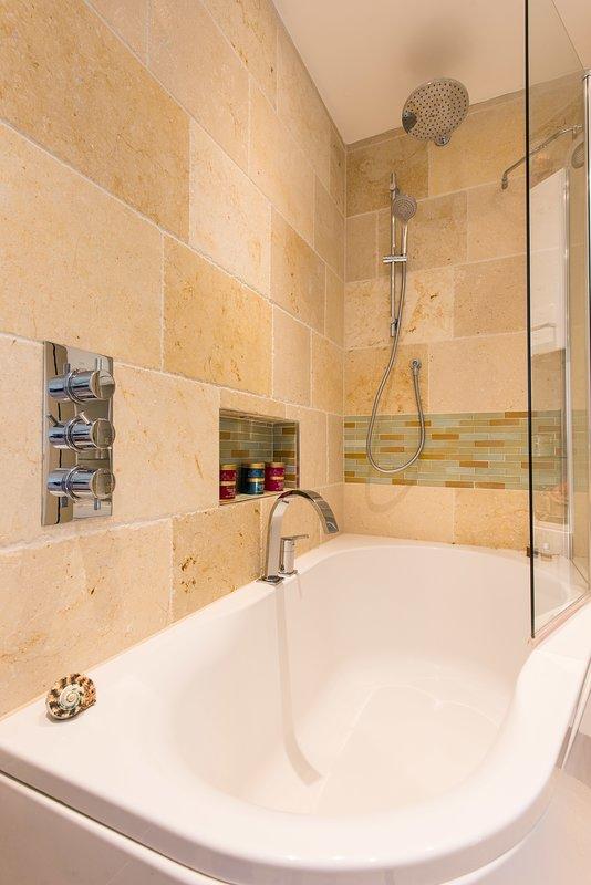 Cuarto de baño con amplia ducha sobre la bañera