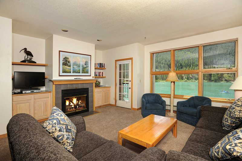 Relax in the cozy living area, complete with fireplace and TV. Views vary.