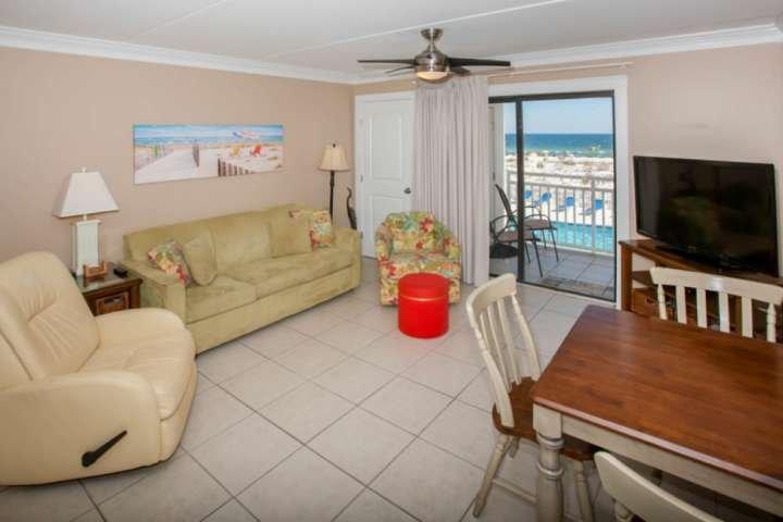 Fliesen- Wohnzimmer mit Deckenventilator mit Blick auf Pool und Golf