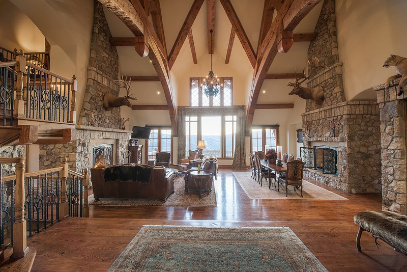 Exposed timber and stone great room with dual gas fireplaces.