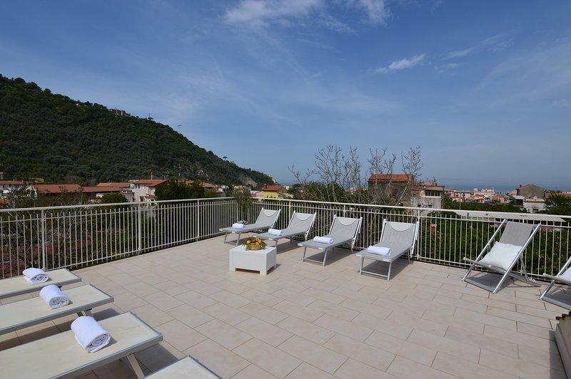 Solarium terrazza esclusiva attrezzata con lettini, sedie a sdraio, doccia, tavoli, sedie e barbecue