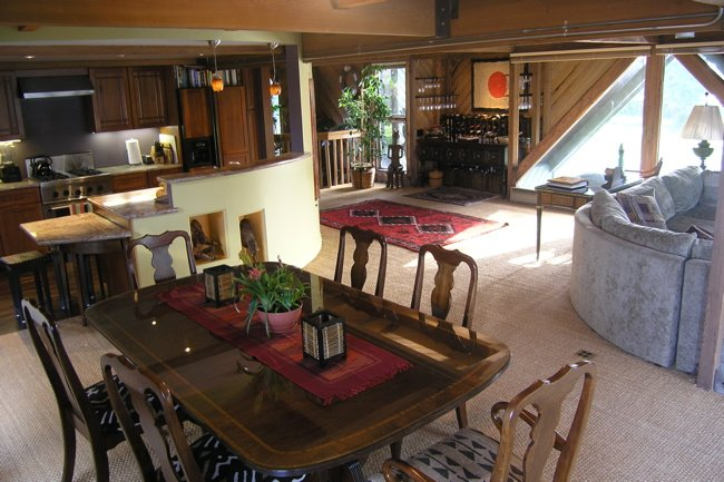 Middle floor dining area with table seating 8 persons. Kitchen in background.