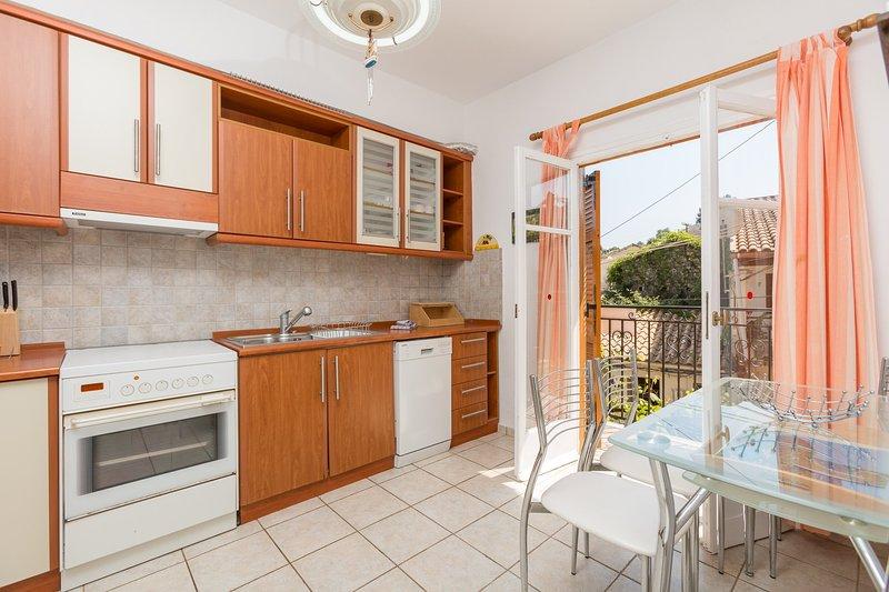 Ausgestattete Küche, Essbereich und Zugang zum Balkon