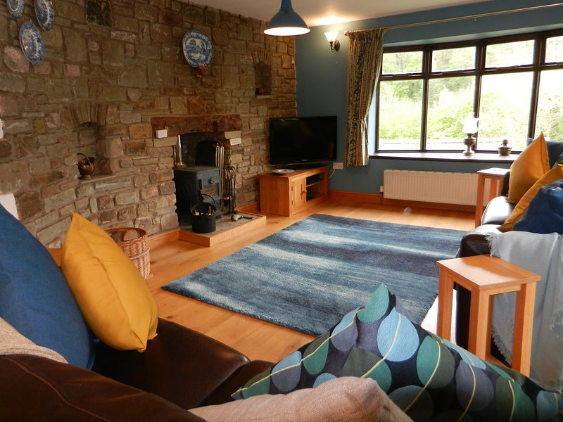 Living Room with log burner, comfortable leather sofas and oak floors, with access onto a  patio.