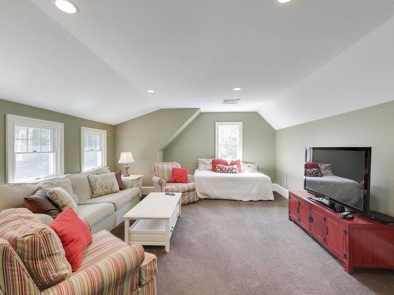 El área del desván cuenta con TV grande, sofá cama y sofá cama para opciones flexibles para dormir