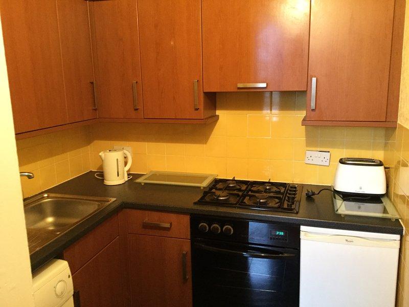 cucina con piano cottura, forno, lavatrice completamente attrezzata.