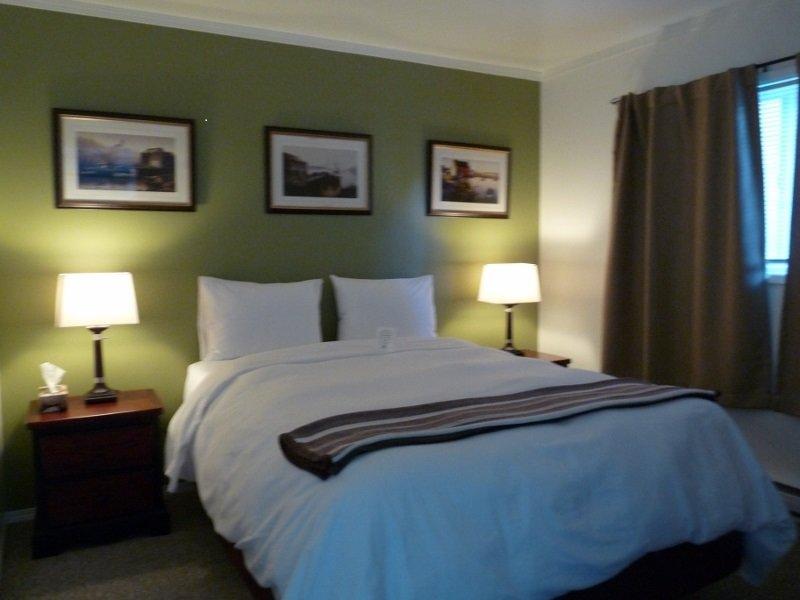 Ett sovrum stuga med fluffly täcke, gott elkontakter, ljus och mörkläggningsgardiner.