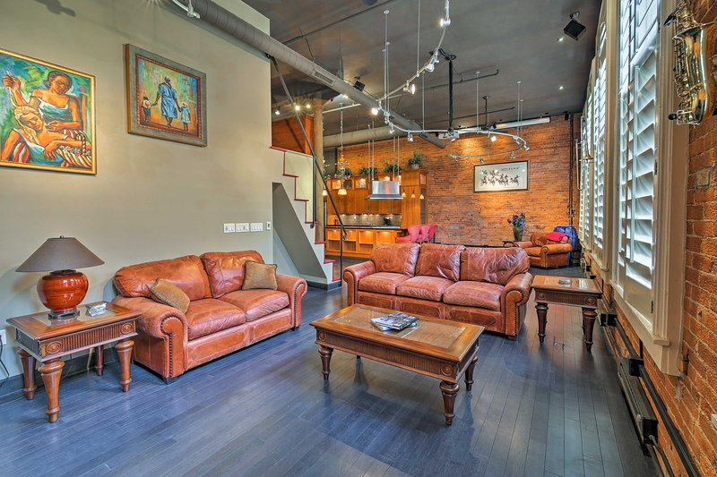 Exposed brick walls and large windows add an urban flare to the living area.