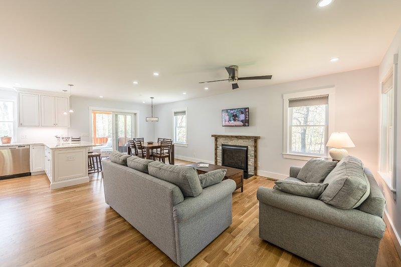 Sala de estar abierta, cocina y comedor con deslizadores de vidrio a porche