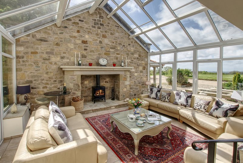 Fantastic light filled conservatory with huge fireplace and woodburning stove. Amazing views.