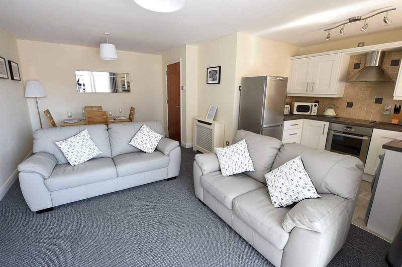 Comfortable living area with 2 leather sofas. There is also a wide screen TV and Bluetooth speaker.
