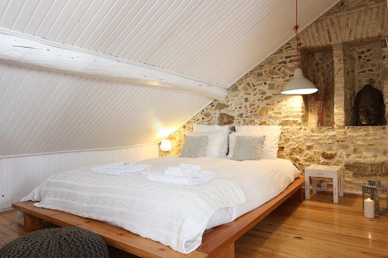 Das große Doppelbett sitzt gegen eine Original, Steinmauer eine rustikale und traditionelle Atmosphäre Hinzufügen