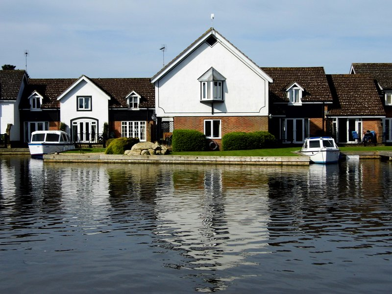 Wherry Cottage (centre) surrounded by landscaped gardens and your own private mooring.