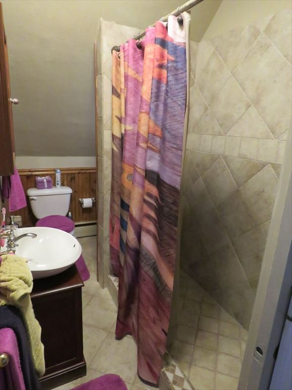 All tile bathroom with step in shower.