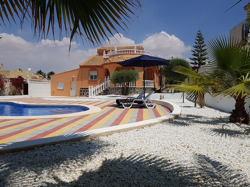 View of the house and the spacious sunbathing area by the pool