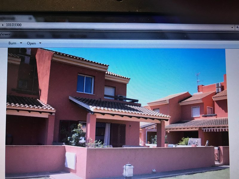 Villa with walled patio and upstairs balcony.