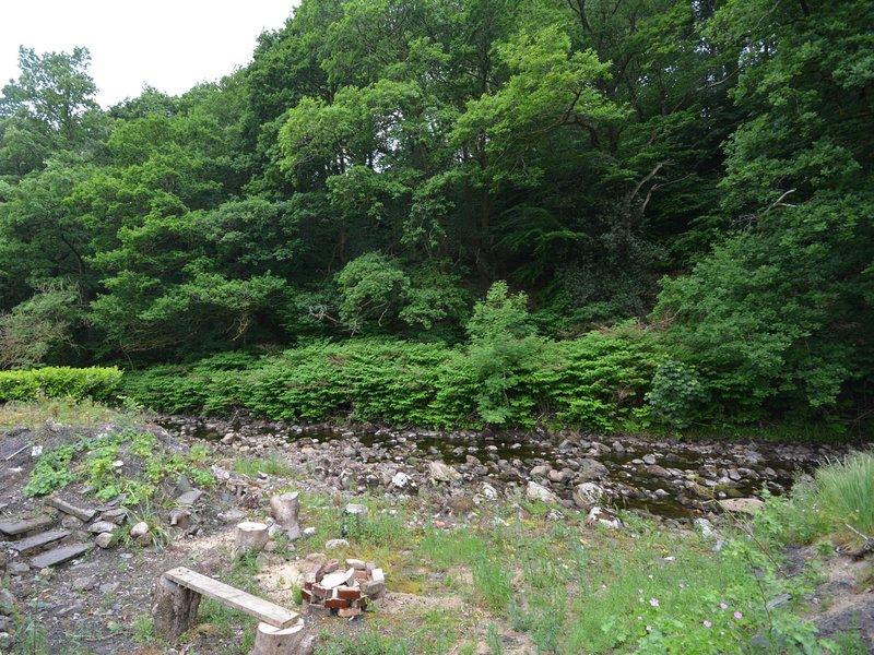El pequeño río con asientos de madera rústica y pozo de fuego
