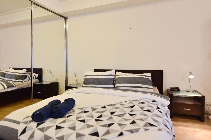Un área de dormitorio con una cama de matrimonio y almohadas de lujo.