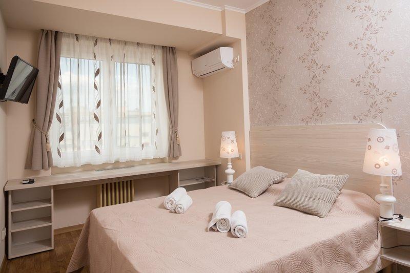 Dormitorio con cama de matrimonio, aire acondicionado y TV