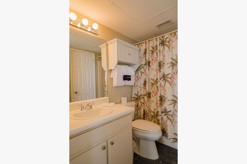 Tropical inspired bathroom has tub/shower combo with a shower massage for relaxing after a 'long hard day' at the beach.