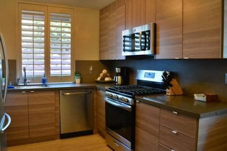 Chefs kitchen with cooktop stove, dishwasher, fridge, and microwave