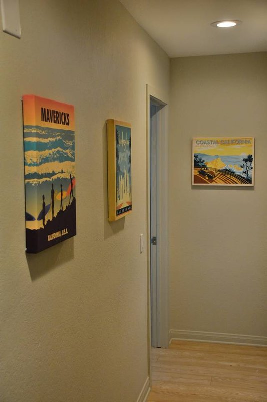 Hallway to bedroom # 2 with fun art and access to washer and dryer
