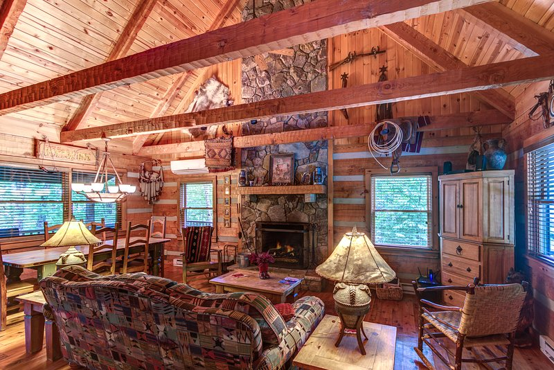 Living room with wood burning fireplace and vaulted beam ceilings