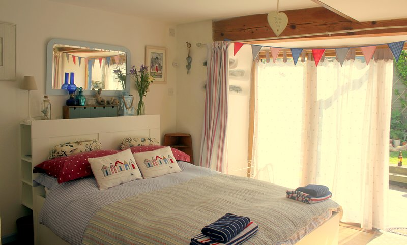 Ty Cert's double bed with views to the garden -  & tri-folding door.