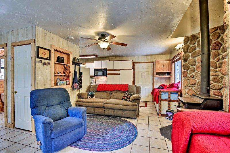O espaço oferece um sofá de pelúcia, poltrona e um fogão a lenha rústico.