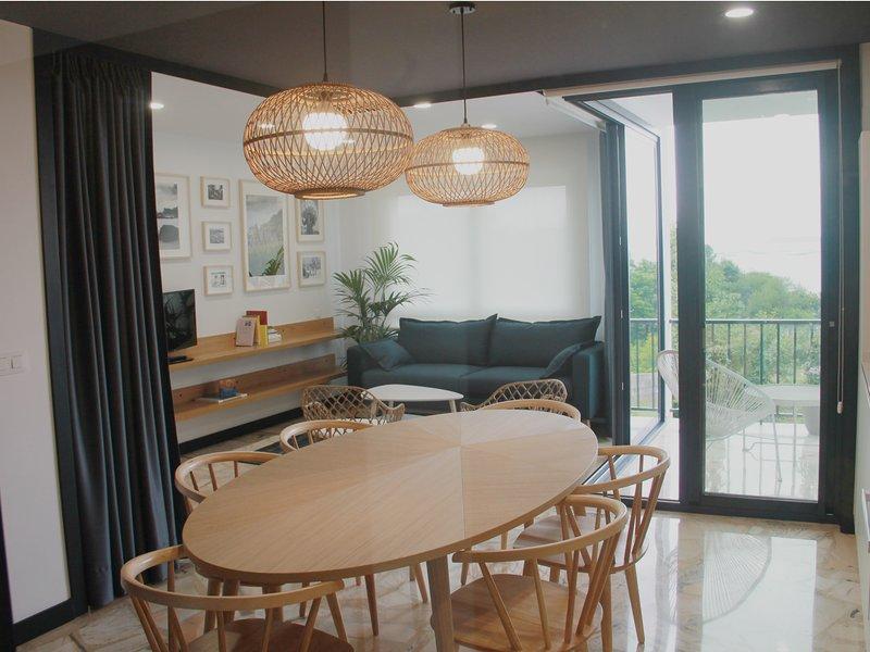 View van het appartement vanaf de ingang met eethoek, een terras en een lounge
