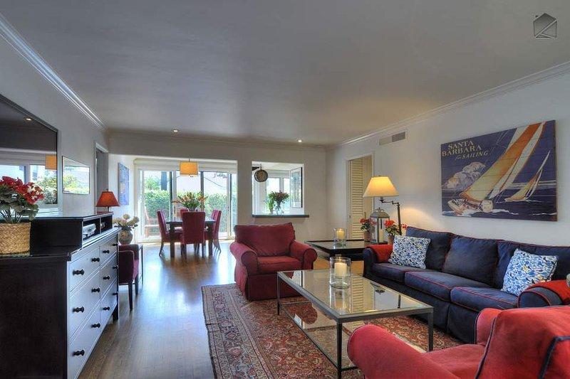 Ver películas en el televisor de pantalla plana en esta cómoda sala de estar con un montón de asientos de lujo, pisos de madera y obras de arte agradable.