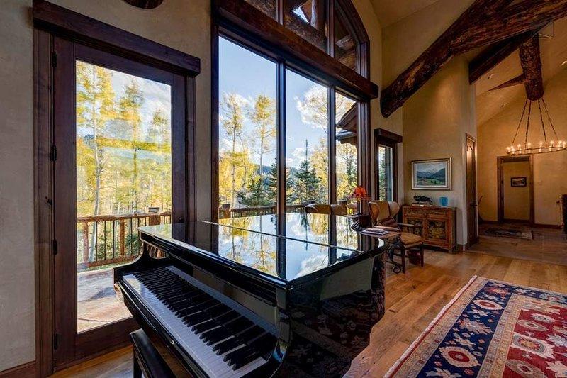 Cosquillas a los marfiles en el piano de cola en el salón de ambiente añadido.