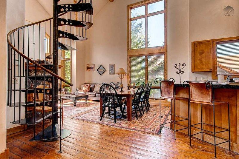 Los altos techos abovedados, una escalera de caracol, y muebles finos irradian lujo en este gran condominio de montaña.