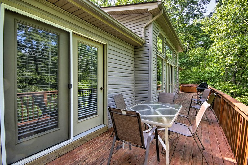 The wraparound porch of this vacation rental house is shrouded in lush foliage.