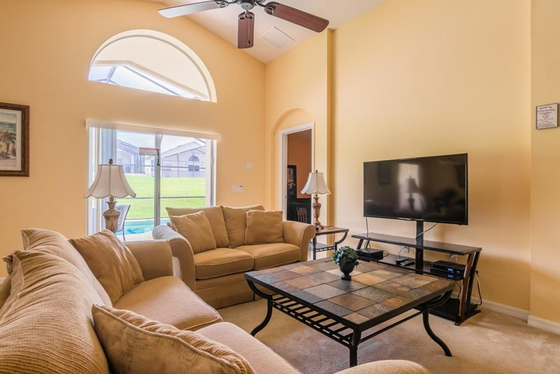La sala de estar de planta abierta, con TV de pantalla plana y puertas de patio a la piscina.