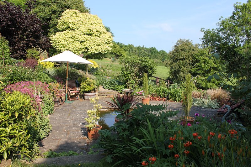 Parasol and seating in the garden by the pond