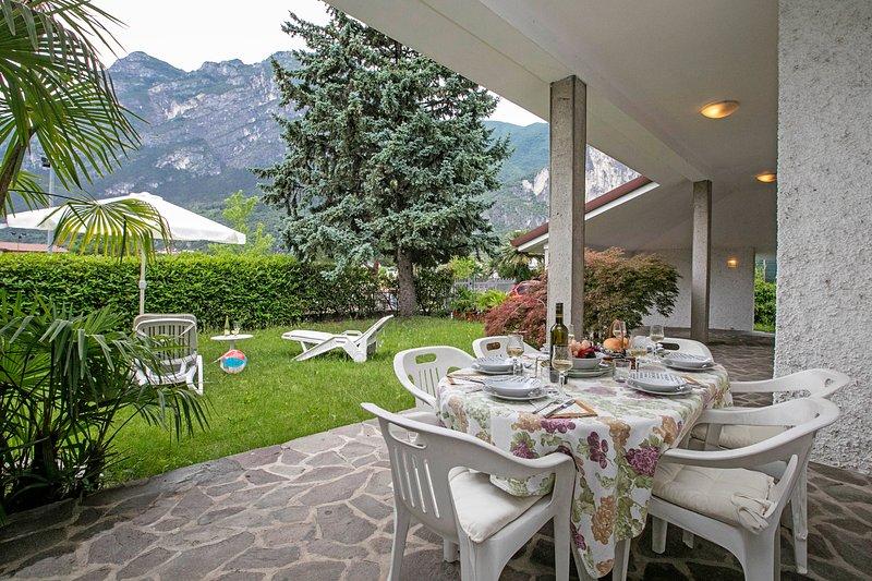 La terraza con mesa de la cena y el césped con camas Sund y sombrilla