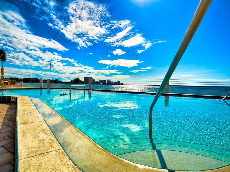 amplia zona de piscina con vistas al agua.
