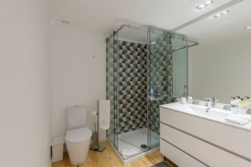 Stylish bathroom fully equipped with shower, hair dryer, fluffy towels, slippers and toiletries.