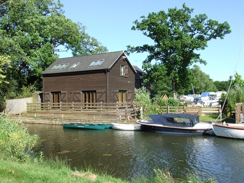 THE BOATHOUSE, woodburner, en-suite bedrooms, views of the lake, near Wroxham, holiday rental in Ludham