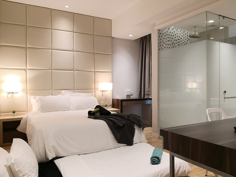 A bedroom area with a queen sized bed, a single sized mattress & plush pillows.