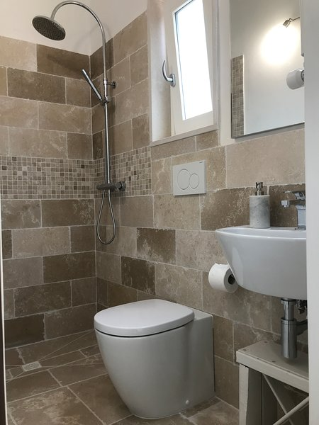 The Peregrine luxury ensuite bathroom with sold chrome rainshower, toilet and sink with stone tiling