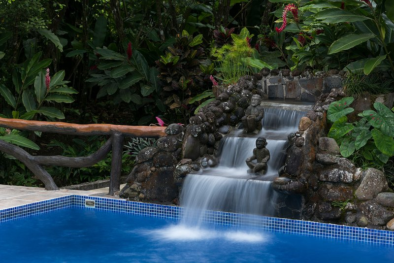 Swimming pool with waterfall and signature wood-designed railing.
