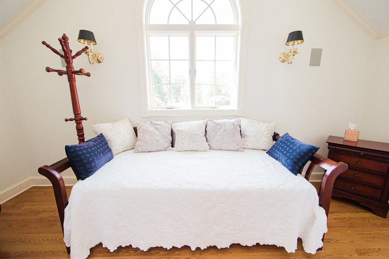 The curtained  nook can be used as a bedroom and has a twin day bed.