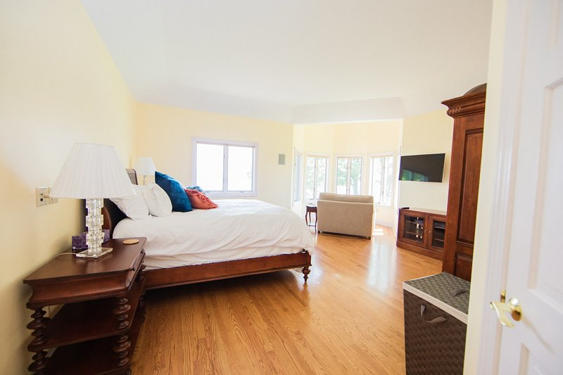 The second floor master (bedroom 3)  has plush king-sized bed, lake views, TV, + sitting area.