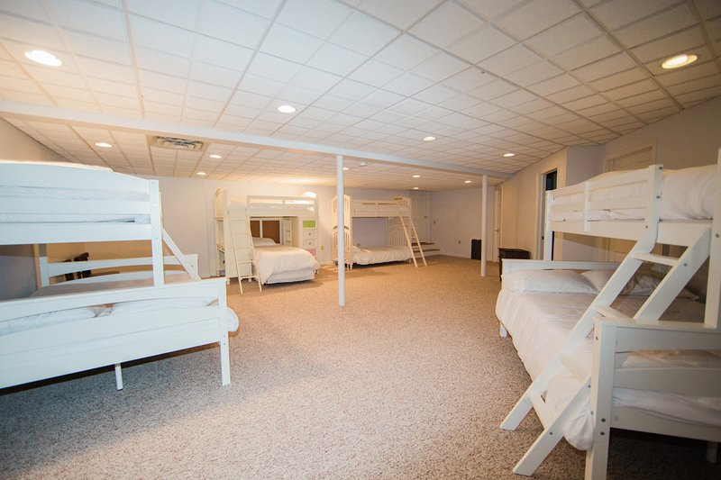 Bedroom area in the finished basement with 6 twin beds and 2 doubles. There is also a full bathroom
