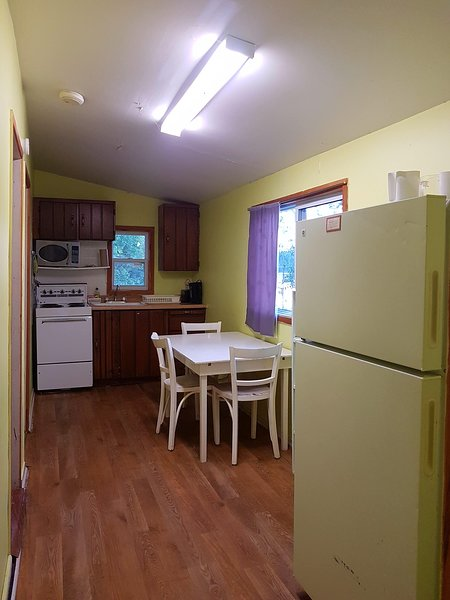Full kitchen with stove. fridge, microwave, coffee maker and toaster. Pots pans dishes and cutlery.