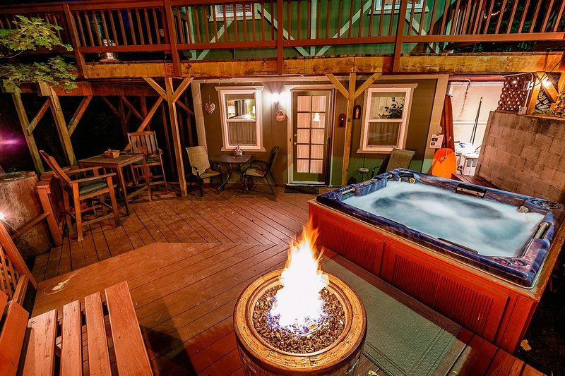 Evening at back patio with hot tub, fire ring & fence lighting